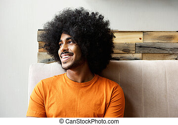 Smiling young black man with afro looking away