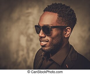 Smiling young black man with sunglasses posing on dark background.