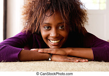Smiling young black woman lying down on floor