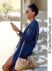 Smiling young black woman outdoors using cell phone
