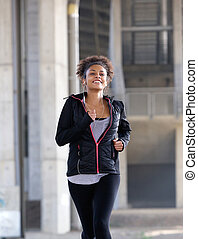 Smiling young black woman running outdoors
