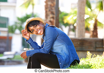 Smiling young black woman sitting in park