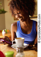 Smiling young black woman using cellphone