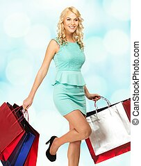 Smiling young blond woman with shopping bags over blurred background