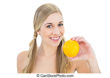 Smiling young blonde woman holding an orange