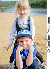 Smiling young boy and girl relaxing on a beach