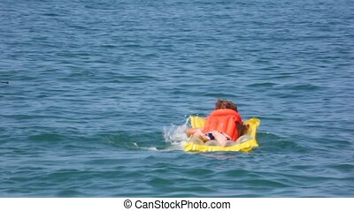 smiling young boy dressed in life jacket oaring on...