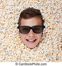 Smiling young boy in stereo glasses looking out of popcorn -...