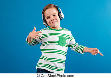 Smiling young boy listening music and dancing
