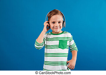 Smiling young boy listening music by headphone