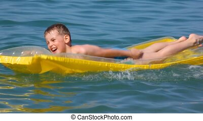 smiling young boy oaring on inflatable mattress in sea