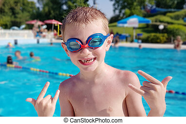 Smiling young boy wearing swimming glasses in swimming pool