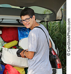 smiling young boy with glasses puts suitcases in the luggage
