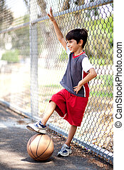 Smiling young boy with his basketball
