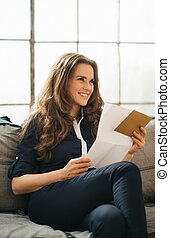 Smiling young brown-haired woman holding letter