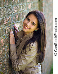 Smiling young brunette against wall