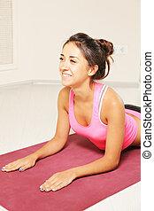 Smiling young brunette at cobra pose