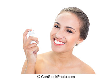 Smiling young brunette woman holding an inhaler