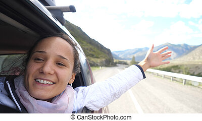 Smiling young brunette woman in a car playing with wind and driving past the beautiful mountains