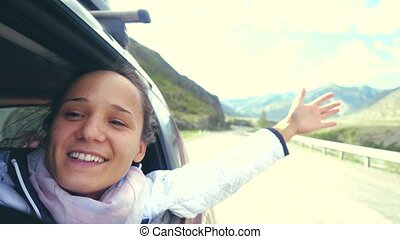 Smiling young brunette woman in a car playing with wind and driving past the beautiful mountains. 3840x2160