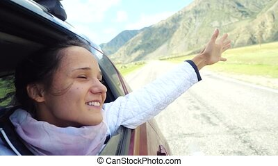Smiling young brunette woman in a car playing with wind and driving past the beautiful mountains.