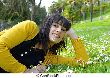 young brunette woman lying in the grass
