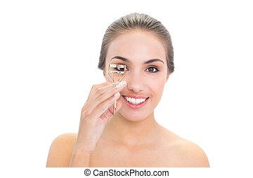 Smiling young brunette woman using an eyelash curler
