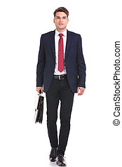 Smiling young business man walking
