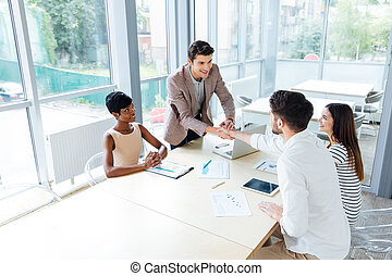 Smiling young business people shaking hands on meeting in office