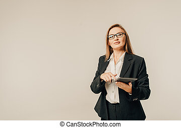 Smiling young business woman in glasses with tablet for notes on toned background