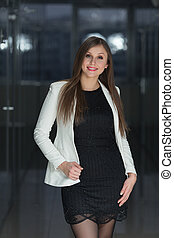 Smiling young business woman in office looking at camera.