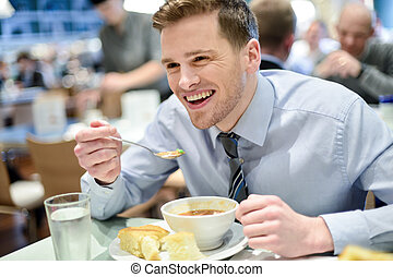 Smiling young businessman having lunch