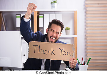 Smiling Young Businessman Holding Cardboard With Thank You Text