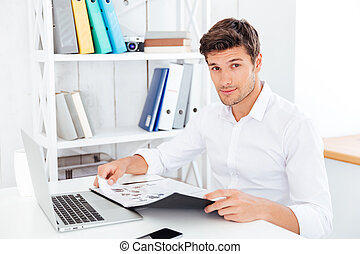 Smiling young businessman holding folder with documents
