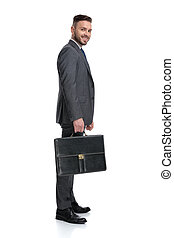 smiling young businessman holding suitcase is waiting in ...