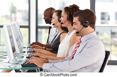 Smiling young businessman in a call center