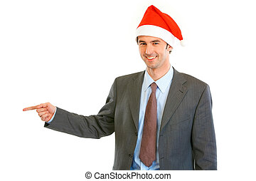 Smiling young businessman in Santa hat pointing finger at copy space isolated on white