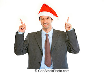 Smiling young businessman in Santa hat pointing finger up at copy space isolated on white