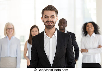 Smiling young businessman looking at camera posing with diverse