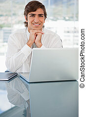 Smiling young businessman resting his head on his hands