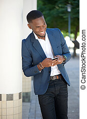 Smiling young businessman sending text message by cellphone
