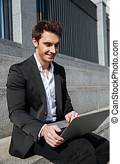 Smiling young businessman sitting outdoors using laptop
