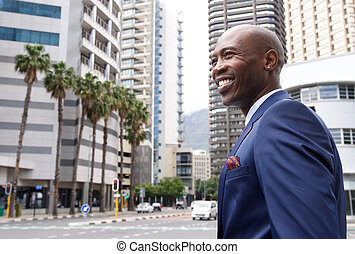 Smiling young businessman standing on the city street