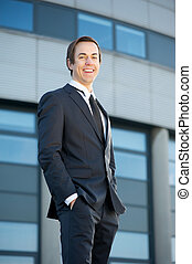 Smiling young businessman standing outdoors