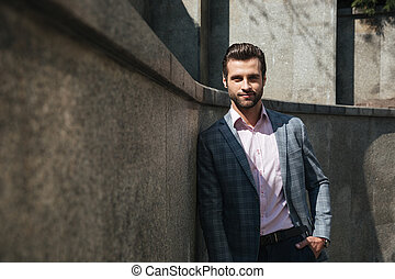 Smiling young businessman walking outdoors