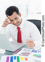 Smiling young businessman with laptop and graphs