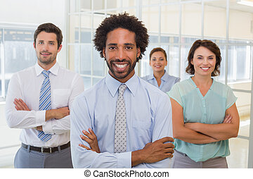 Smiling young businessman with colleagues in office
