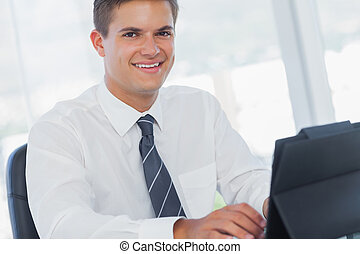 Smiling young businessman working on his tablet pc