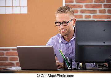 Smiling Young Businessman Working On Laptop