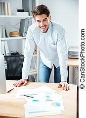 Smiling young businessman working with documents at workplace